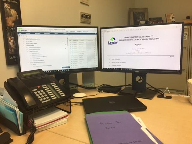 Desktop computers in Langley's office using eSCRIBE software